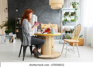 Young attractive woman making craft in stylish contemporary apartment