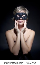 Young attractive woman with mask  on black background