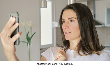 Young attractive woman with mask under eyes using smartphone. Beautiful female with natural makeup, have collagen patches on fresh facial skin in home.