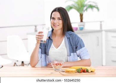 Young attractive woman with milk and healthy breakfast in kitchen