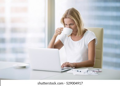 Young attractive woman at modern office desk, working with laptop, drinking coffee, having lunch in a hurry, no time for break, millennial staring at screen even during meal. Business concept photo