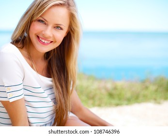 Young attractive woman near the ocean on a summer day