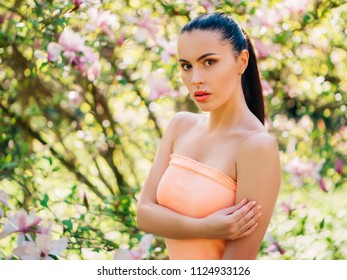 Young attractive woman on a background of magnolias in a park with bright sunlight
