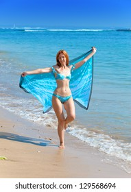 The young attractive woman on a beach with a blue scarf in hands