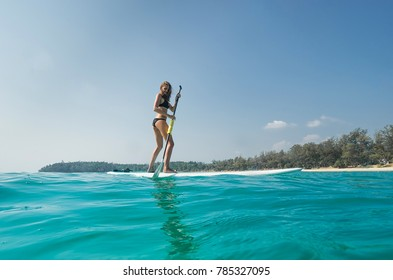 Young attractive woman on stand up paddle board, SUP(padleboarding), in the Andaman sea, Thailand. Active life concept.