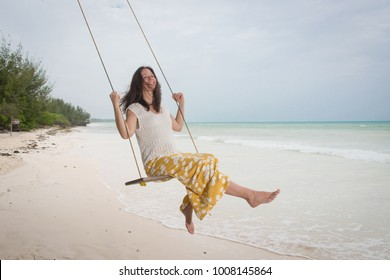 Young attractive woman on a swing at a tropical beach, Zanzibar