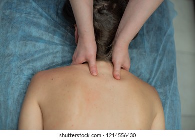 Young attractive woman osteopath doing back massage. Blonde on a session of manual therapy. A professional masseuse does a back massage for a girl in the spa salon.