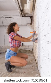 young attractive woman paints white brick wall with paint brush