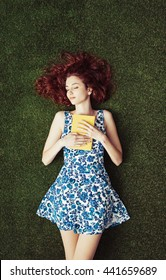Young attractive woman at the park, she is lying down, holding a book and relaxing