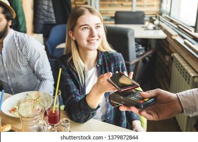 Junge attraktive Frau, die im Café mit kontaktloser Smartphone-Zahlung bezahlt