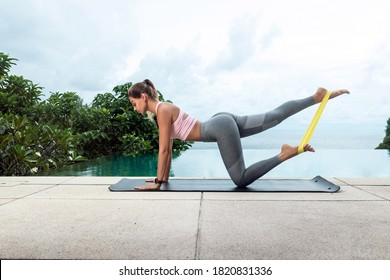 Young attractive woman performing bodyweight fitness training on the nature near infinity pool. Beautiful female doing donkey kick buttocks exercise.