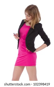 Young attractive woman in pink dress and black coat is using her mobile phone over white background
