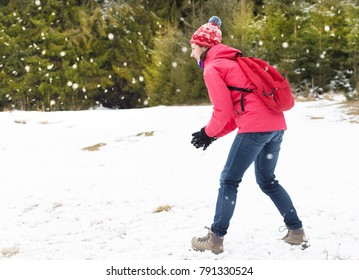 Young attractive woman  playing  in the snow. Winter holiday fun