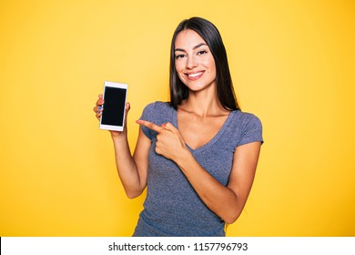 Young attractive woman is pointing on blank screen of phone in her hand and looks into a camera