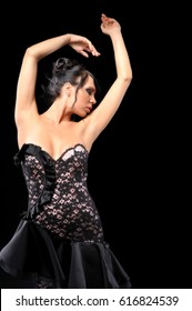 young attractive woman posing in elegant dress on black background