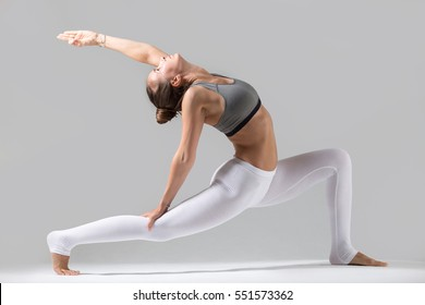 Young attractive woman practicing fitness, standing in lunge exercise, yoga pose, working out wearing sportswear, white pants, gray top, indoor full length, isolated, grey studio background