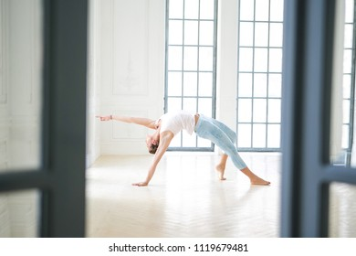 Young attractive woman practicing yoga. Working out wearing sportswear, white T-shirt and blue pants. Stretching in Wild Thing, Flip-the-Dog exercise, Camatkarasana pose