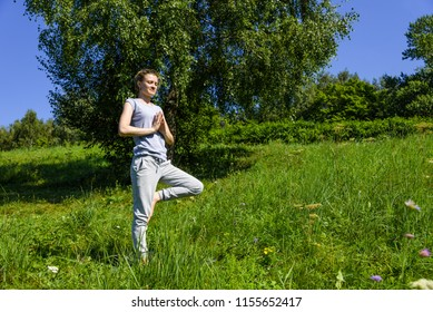 Young attractive woman practicing yoga outdoors on a sunny day, Vrikshasana (tree pose)