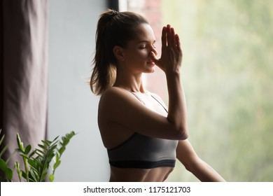 Young attractive woman practicing yoga, doing Alternate Nostril Breathing exercise, nadi shodhana pranayama pose, working out, wearing sportswear, grey top, indoor close up, yoga studio, side view