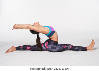 Young attractive woman practicing yoga doing Hanumanasana, Splits Pose, Monkey Pose in full length, isolated over white studio background
