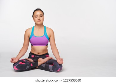 Young attractive woman practicing yoga, doing Padmasana, lotus pose in full length with closed eyes, isolated over white studio background