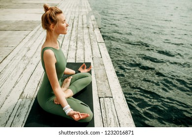 Young attractive woman practicing yoga in lotus asana. Outdoor. Toned.