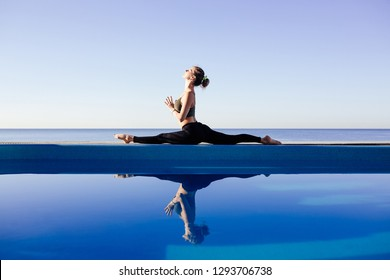 Young attractive woman practicing yoga stretching in One Legged King Pigeon exercise, Eka Pada Raja Kapotasana working out by pool, above beach, relaxing against blue sky. Health and beauty concept