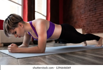 Young attractive woman practicing yoga, standing in Push ups or press ups exercise, Plank pose, working out, wearing sportswear, side view
