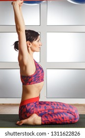 Young attractive woman practicing yoga at fitnes club, sitting in Virasana exercise, Hero pose with namaste, working out, wearing sportswear, red pants and top, indoor full length