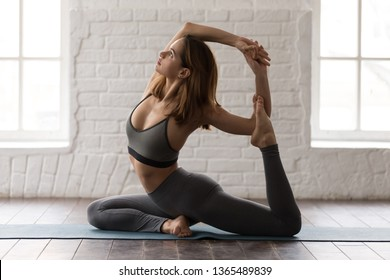 Young attractive woman practicing yoga at home or in yoga studio, beautiful girl in grey sportswear, leggings and bra standing in Mermaid pose, doing Eka Pada Rajakapotasana exercise, working out