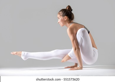 Young attractive woman practicing yoga, standing in Leg over shoulder, Elephant Trunk exercise, Eka Hasta Bhujasana pose, working out wearing sportswear, indoor full length, grey studio background