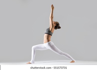 Young attractive woman practicing yoga, standing in Warrior one exercise, Virabhadrasana I pose, working out wearing sportswear, indoor full length, isolated against grey studio background