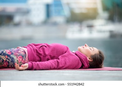 Young attractive woman practicing yoga, lying in Dead Body exercise, Savasana, Corpse pose, relaxing, refreshing after sport, wearing nice pink sportswear, outdoor city, river background, close up