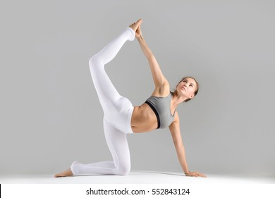 Young attractive woman practicing yoga, stretching in Bird dog exercise, tiger pose, working out wearing sportswear, white pants, bra, indoor full length, isolated against grey studio background