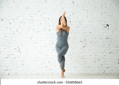 Young attractive woman practicing yoga, standing in Eagle exercise, Garudasana pose, working out, wearing sportswear, grey suit, indoor full length, white studio background