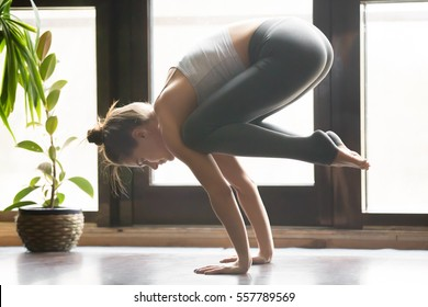 Young attractive woman practicing yoga, standing in Crane, Bakasana pose, working out, wearing sportswear, grey pants, bra, indoor full length, home interior background, living room