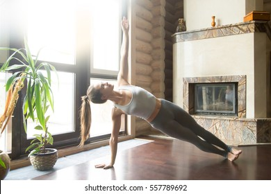 Young attractive woman practicing yoga near fireplace, standing in Side Plank exercise, Vasisthasana pose, working out, wearing sportswear, grey pants, bra, indoor full length, home interior