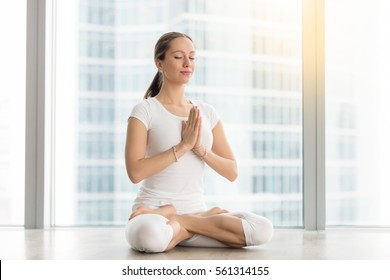 Young attractive woman practicing yoga, sitting in Padmasana, exercise, Lotus pose, namaste, working out, wearing sportswear, white t-shirt, pants, indoor full length, near floor window with city view