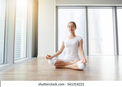 Young attractive woman practicing yoga, sitting in Ardha Padmasana exercise, Half Lotus pose, working out, wearing white t-shirt, pants, meditation session at floor window with city view. Full length