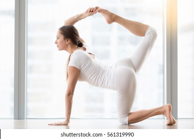 Young attractive woman practicing yoga, stretching in Bird dog exercise, tiger pose, working out, wearing sportswear, white t-shirt, pants, indoor full length, near floor window with city view