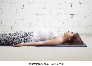 Young attractive woman practicing yoga, lying in Dead Body, Savasana exercise, resting in Corpse pose, working out wearing sportswear, indoor, white loft studio background, closeup