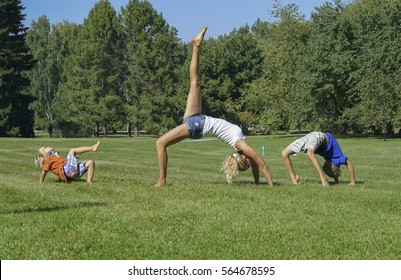 Young attractive woman practicing yoga with kids on green grass, standing in Bridge exercise, One legged Wheel pose.