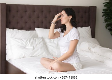 Young attractive woman practicing yoga at home or hotel, sitting on bed and doing Alternate Nostril Breathing exercise, nadi shodhana pranayama working out, wearing white casual clothes, full length