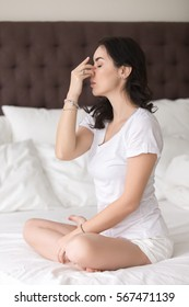 Young attractive woman practicing yoga at home, sitting in Sukhasana pose, Alternate Nostril Breathing exercise, nadi shodhana pranayama, working out wearing white casual clothes, full length, bedroom