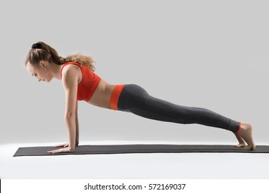 Young attractive woman practicing yoga, doing Push ups or press ups exercise, Plank pose, working out, wearing sportswear, red tank top, pants, indoor full length, isolated, grey studio background
