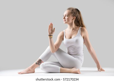 Young attractive woman practicing yoga, sitting in Ardha Matsyendrasana exercise, Half lord of the fishes pose, working out, wearing sportswear, white tank top, pants, indoor full length, grey studio