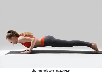 Young attractive woman practicing yoga, standing in four limbed staff exercise, doing Push ups or press ups, chaturanga dandasana pose, working out, wearing red tank top, pants, full length, studio