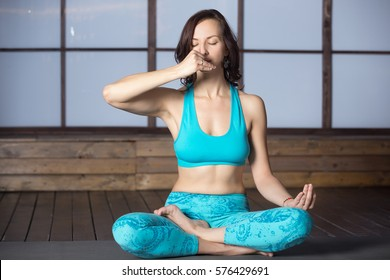 Young attractive woman practicing yoga, sitting in Half Lotus pose, making Alternate Nostril Breathing, working out, wearing sportswear, blue tank top, pants, indoor full length, evening practice