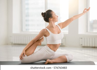 Young attractive woman practicing yoga, sitting in One Legged King Pigeon exercise, Eka Pada Rajakapotasana pose, working out, wearing sportswear, sport bra, pants, full length, white color background