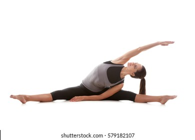 Young attractive woman practicing yoga, sitting in Upavistha Konasana exercise, side bend, working out, wearing sportswear, grey tank top, black pants, full length, isolated, white studio background